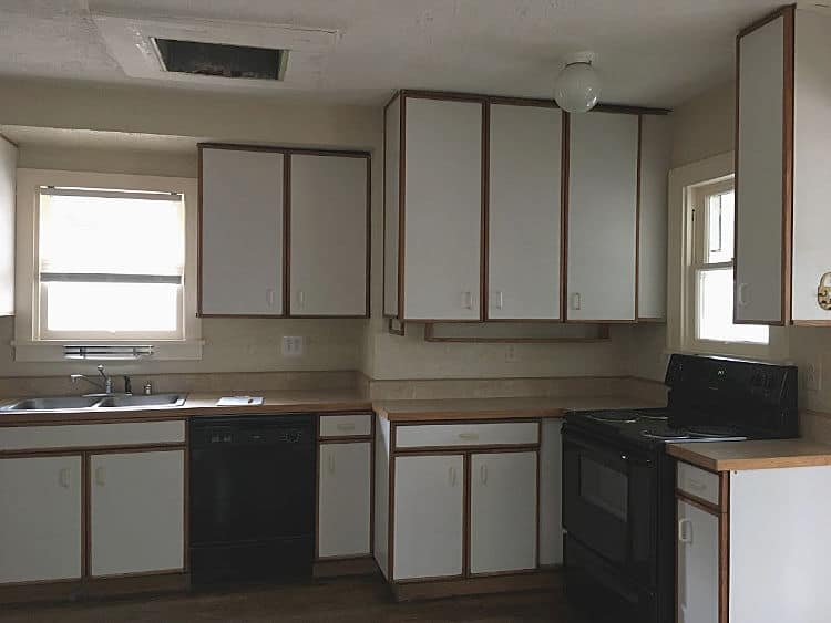 Dark kitchen with dated white particle board cabinets