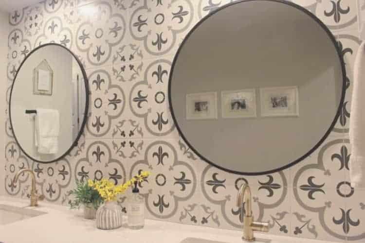 Round mirror hanging on patterned tile backsplash