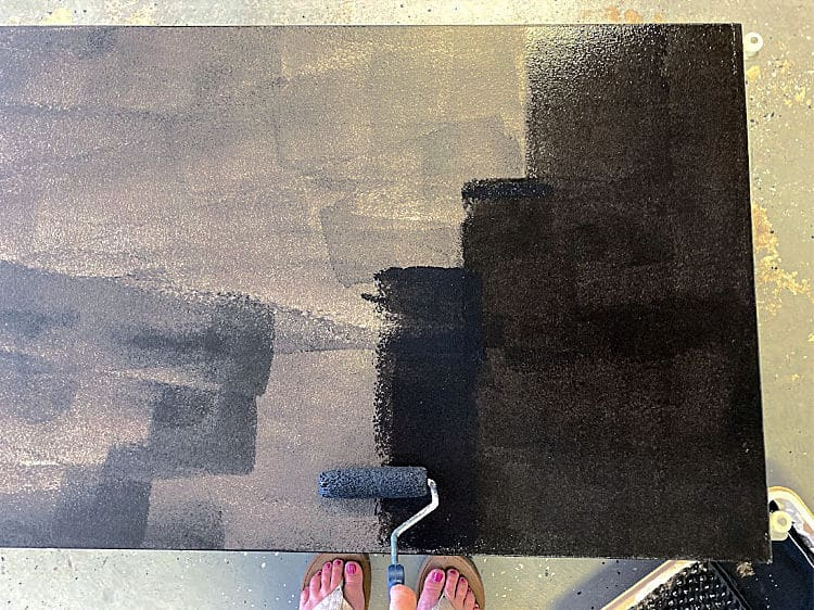 Rolling a second coat of black chalkboard paint on a door, in the opposite direction of the first coat.