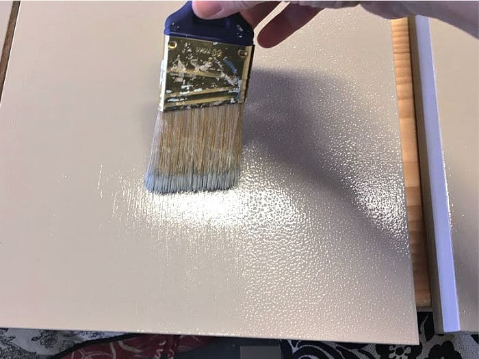 Dragging a dry paint brush through wet paint to get rid of roller marks