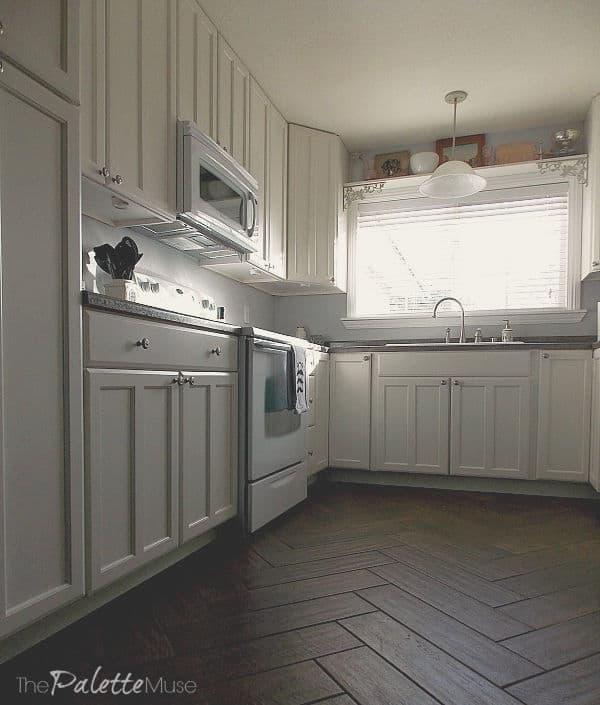 White kitchen cabinets on dark wood floor.