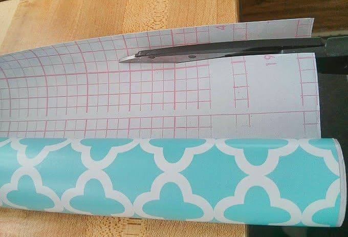 Cutting adhesive shelf paper using grid as a guide