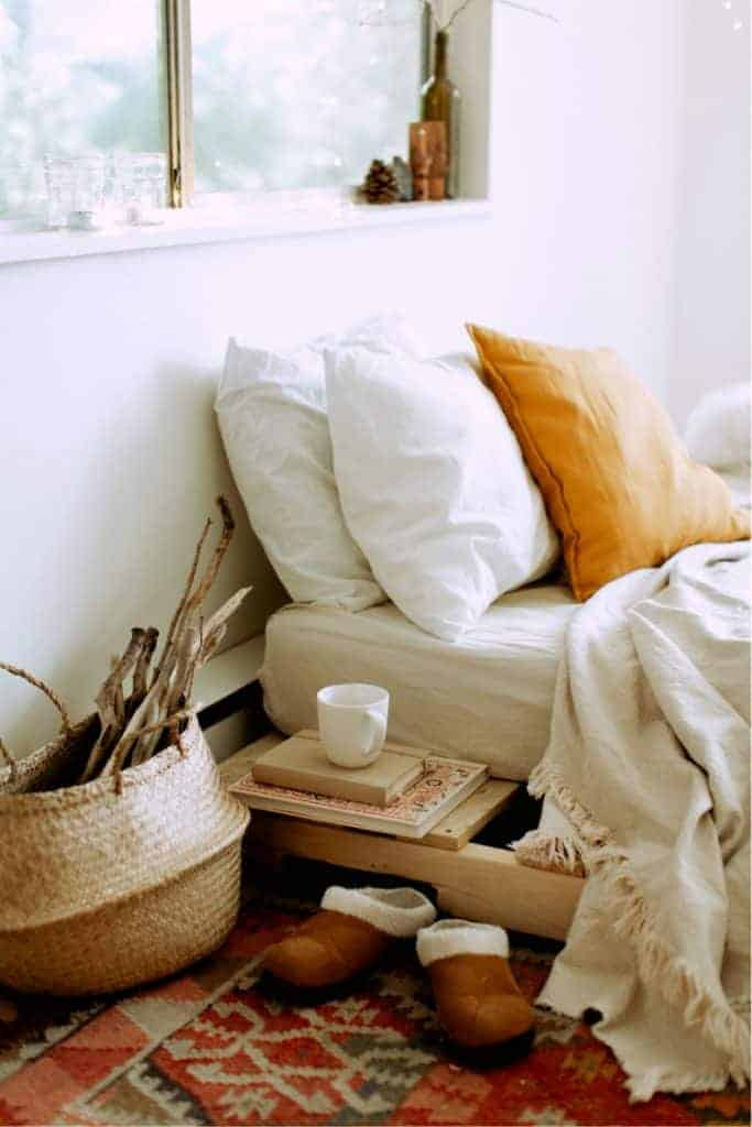 A cozy bed with warm blankets, and slippers on the floor