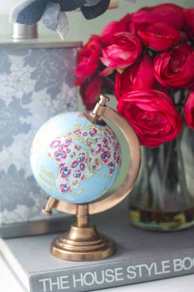 Floral globe on book with vase of flowers
