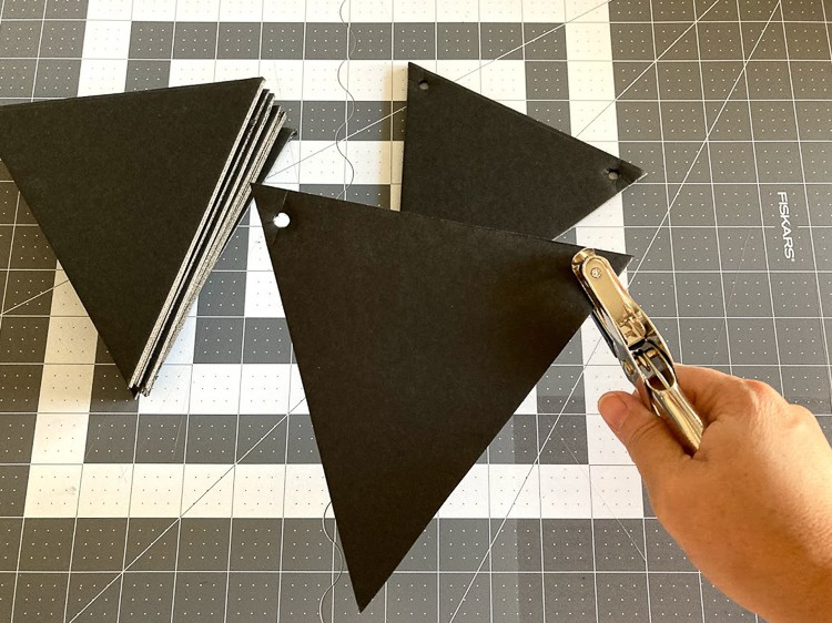 Punching holes in foam board for a chalkboard banner