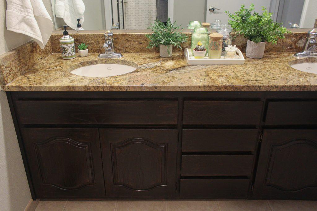 Dark brown stained vanity in updated girls bathroom
