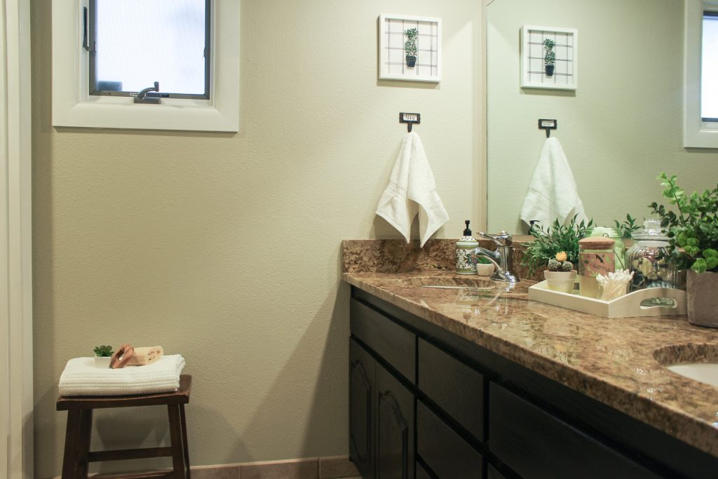 Girls' bathroom with neutral green walls and dark brown vanity