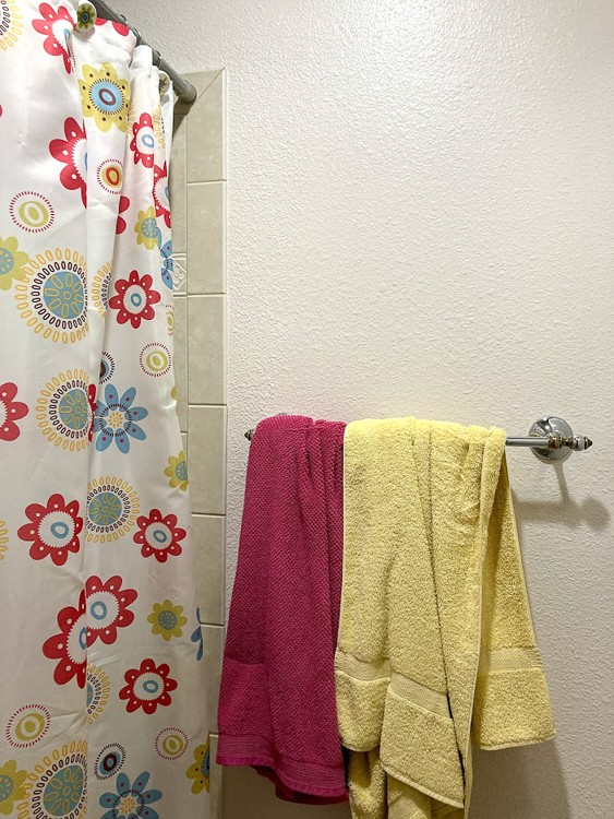 A pink and yellow towel hanging messily from outdated towel bar.