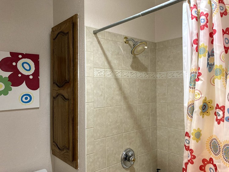 Brown cabinet next to beige shower with red flower shower curtain.