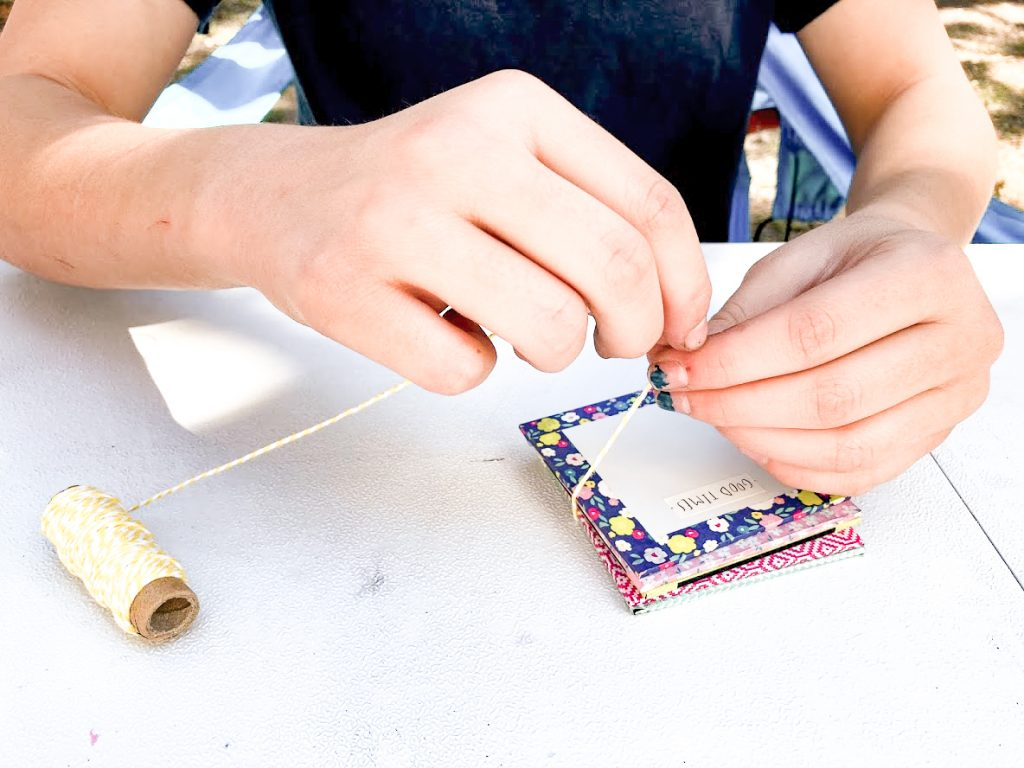 Tying a mini flower press together to preserve the blooms