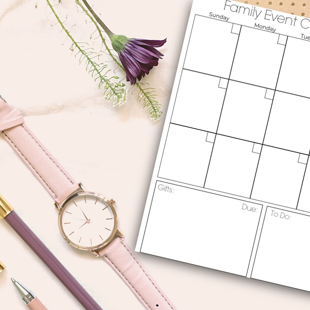 Family Event Calendar on table with watch and pens