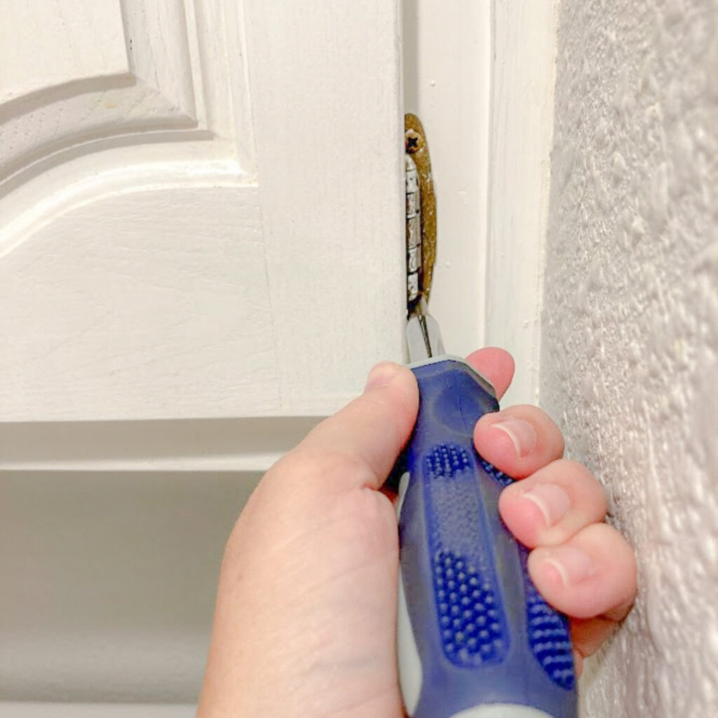 Using a handheld screwdriver to remove screws from cabinet hinges