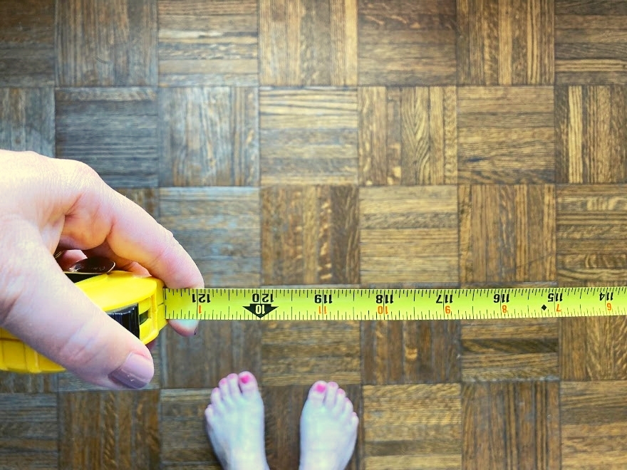 Woman holding tape measure above floor