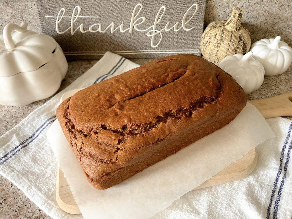 Pumpkin bread on a bread board in front of a sign that says thankful.