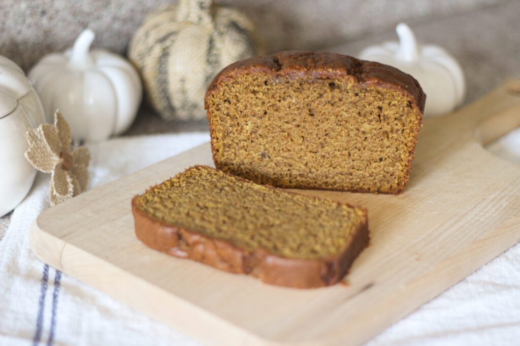 Perfect pumpkin bread sliced on bread board to show moist texture inside
