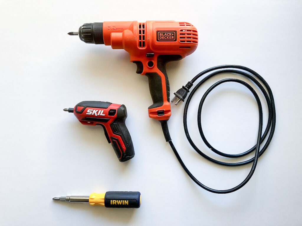 A handheld screwdriver, a small electric screwdriver, and a corded drill.