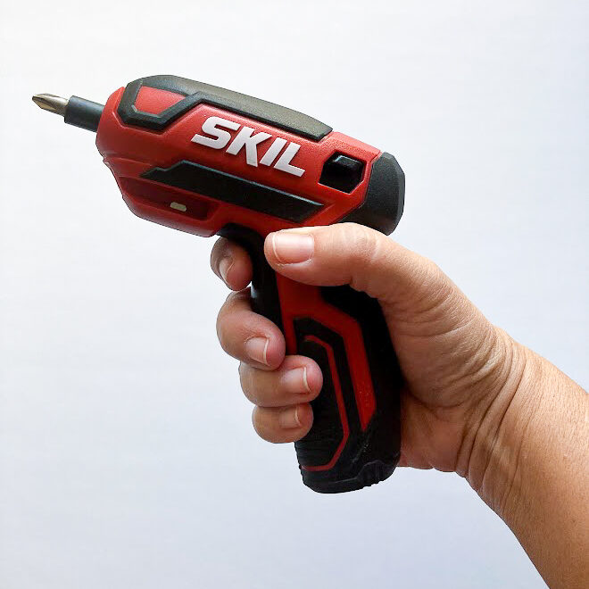 A hand holding a small Skil rechargeable screwdriver